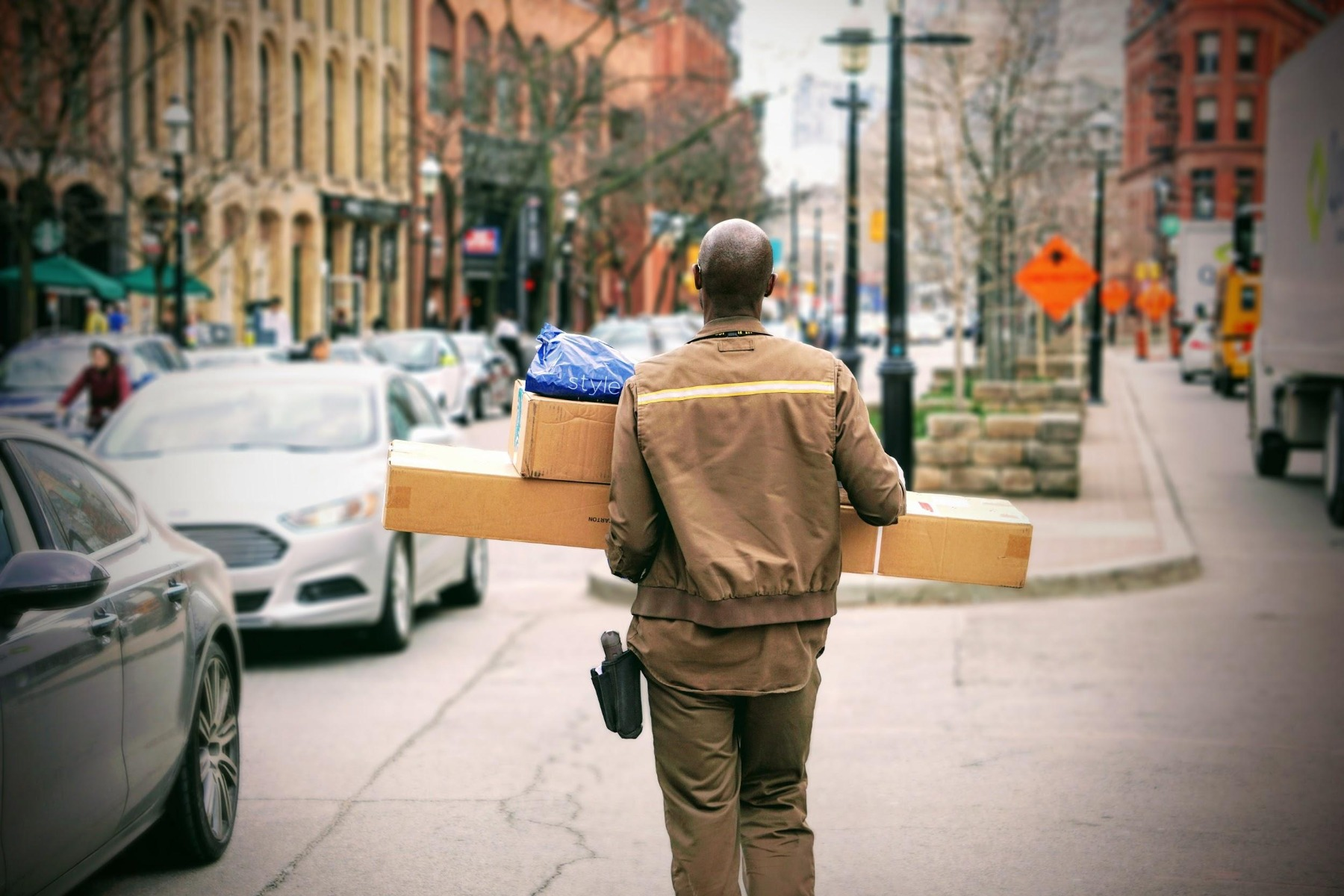 Delivery man on street carrying packages