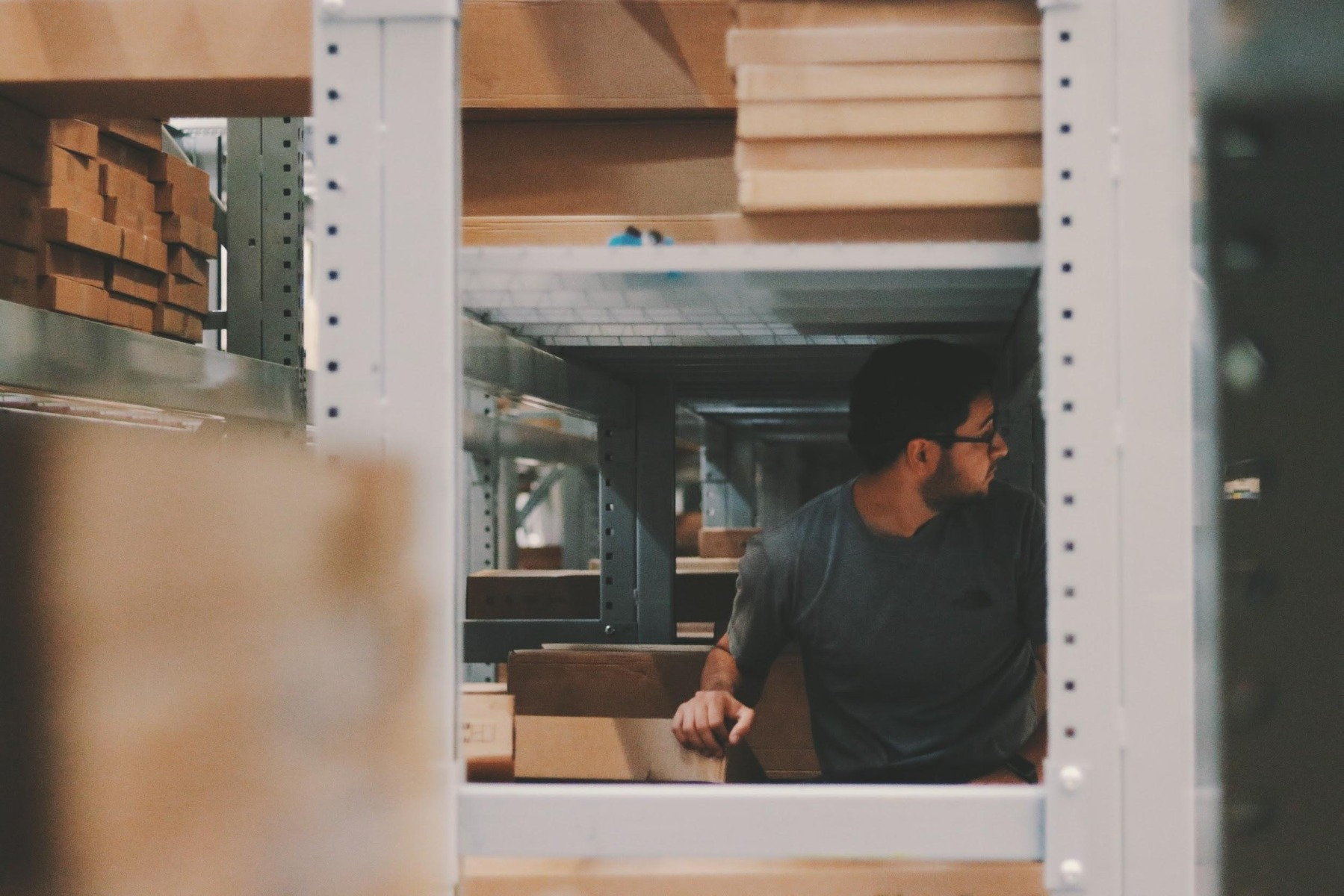 Man under shelf with cardboard boxes