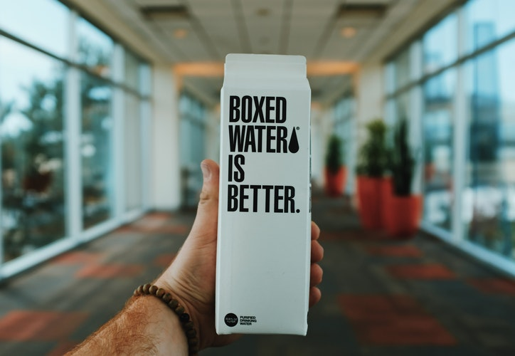 Man holding carton of water with slogan